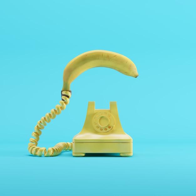 Banaantelefoon met gele uitstekende telefoon op blauwe pastelkleurachtergrond. minimaal idee concept. Premium Foto