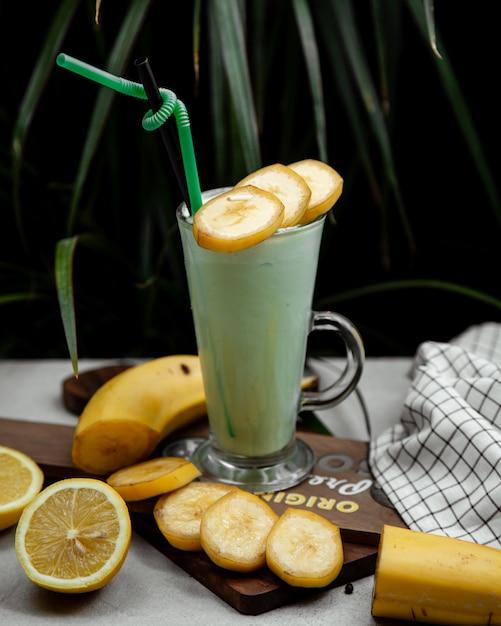 Bananenmilkshake met verse plakjes banaan Gratis Foto