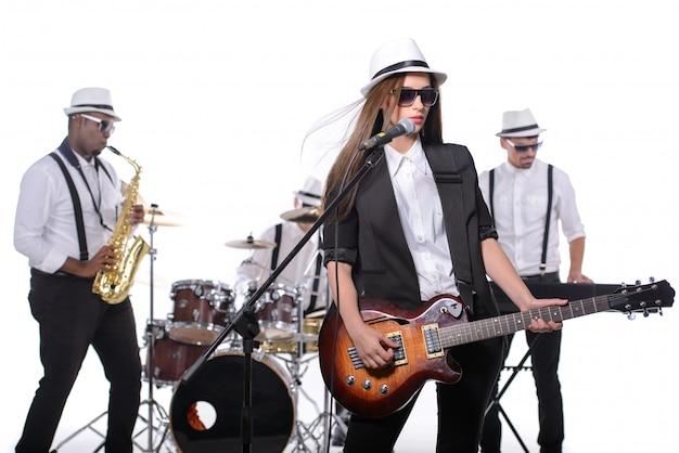 Band van muzikanten met instrumenten in witte kamer. Premium Foto