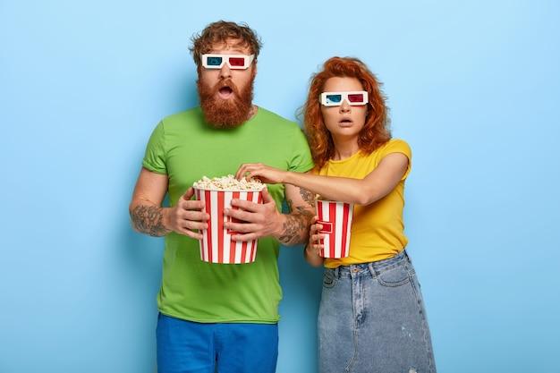 Bang gemberkoppel kijkt enge film, staar stomverbaasd, eet popcorn, draagt een stereoglazen Gratis Foto