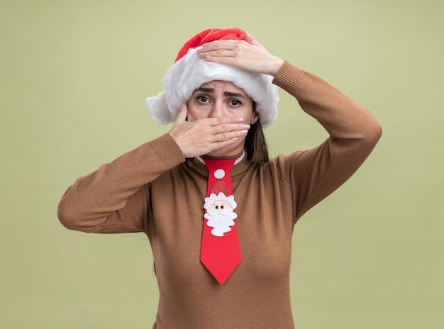 Bang jong mooi meisje met kerstmuts en stropdas bedekt gezicht met hand geïsoleerd op olijfgroene achtergrond Gratis Foto