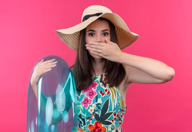 Bang jonge vrouw die hoed draagt die zwemt en hand op haar mond houdt op geïsoleerde roze muur Gratis Foto