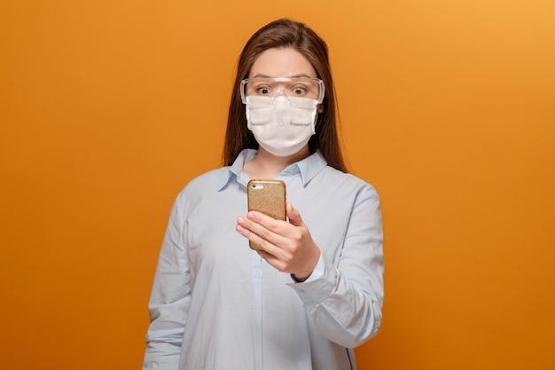 Bang jonge vrouw met een medisch masker op haar gezicht kijkt naar de telefoon, vrouw in paniek over epidemie Premium Foto