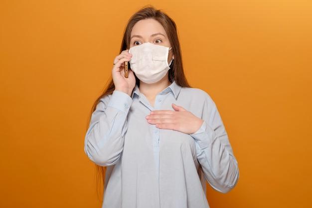 Bang jonge vrouw met medische masker op haar gezicht kijkt naar telefoon, vrouw in paniek over epidemie, praten aan de telefoon Premium Foto