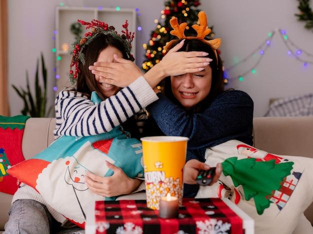 Bang mooie jonge meisjes met hulstkrans en rendieren hoofdband sluiten elkaar ogen met hand zittend op fauteuils kerstmis tijd thuis Gratis Foto