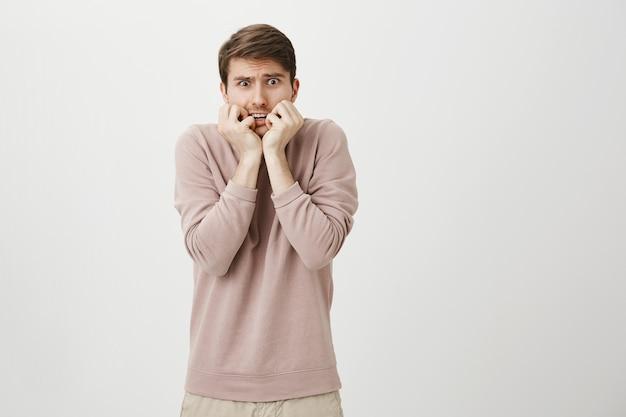 Bang, onzekere jongeman die geschrokken kijkt, bijtende nagels bang Gratis Foto