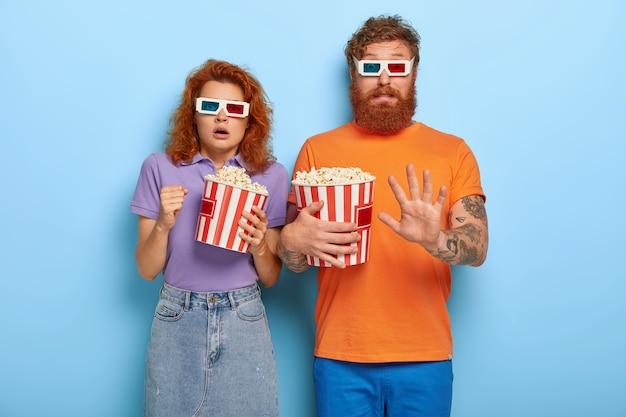 Bang roodharige vriend en vriendin eten popcorn en kijken horrorfilm Gratis Foto