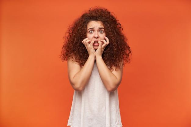 Bang uitziende vrouw, meisje met rood krullend haar. witte off-shoulder blouse dragen. haar gezicht aanraken. heeft angst op haar gezicht. geschokt, geïsoleerd over oranje muur Gratis Foto