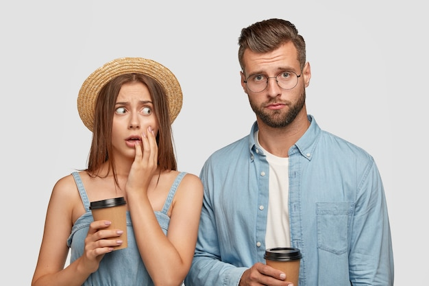 Bange jonge europese vrouw in strooien hoofddeksel kijkt angstig naar zijn metgezel die gefrustreerd gelaatstrekken Gratis Foto