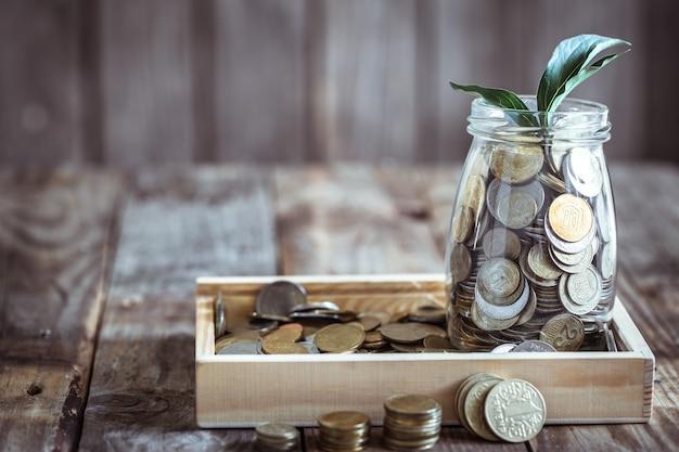 Bank met munten en groene spruit Gratis Foto