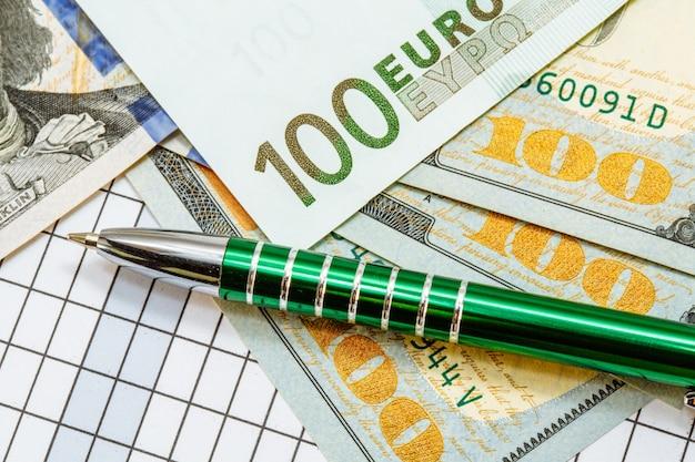 Bankbiljetten honderd dollar en honderd euro lagen op geruit met een groene pen. Premium Foto
