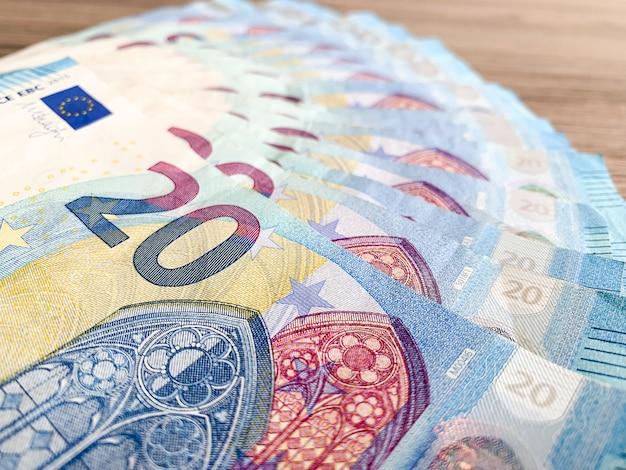 Bankbiljetten met een nominale waarde van twintig euro die als een ventilator op tafel liggen Premium Foto