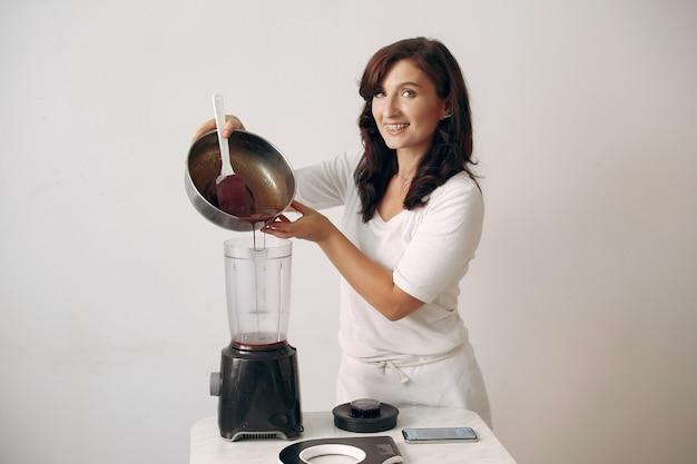 Banketbakker mengt de ingrediënten. dame bereidt dessert. vrouw bakt een cake. Gratis Foto