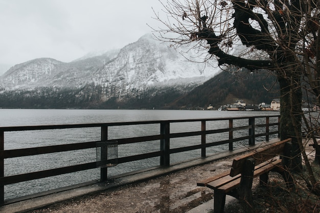 Bankje in de buurt van het meer op een koude dag en besneeuwde bergen Gratis Foto