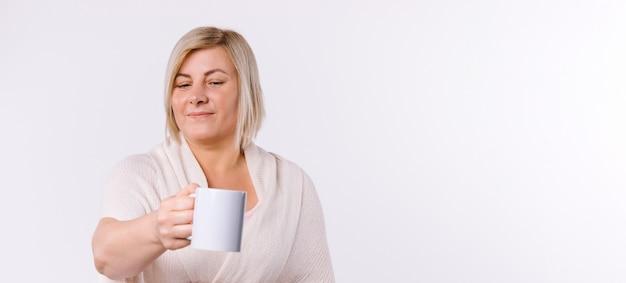 Banner. de blanke vrouw steekt een kopje thee naar de camera. witte achtergrond en lege advertentieruimte. hoge kwaliteit foto Premium Foto