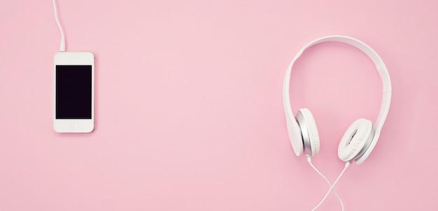 Banner met de mobiele telefoon en koptelefoon op de roze achtergrond. muziek, amusement, online afspeellijsten Premium Foto