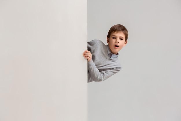 Banner met een verrast kind dat aan de rand gluurt Gratis Foto