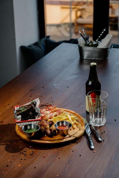 Barbecue gegrilde kippenvleugels close-up met frietjes, saus op een houten bord. vlees voedsel concept gebakken kip benen met franse frietjes bovenaanzicht Premium Foto