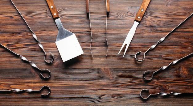 Barbecue gereedschap ingesteld op houten tafel Gratis Foto
