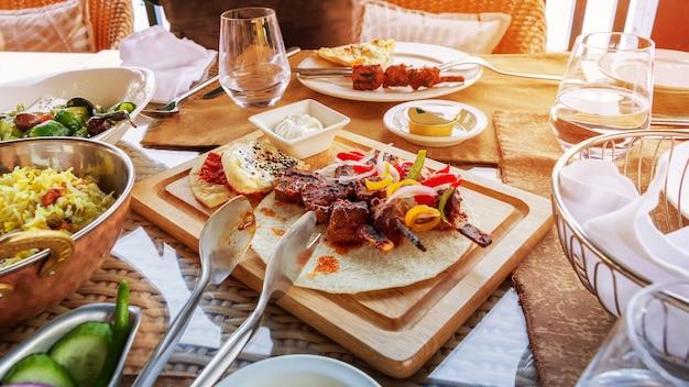 Barbecue grill vlees geserveerd met groenten tortilla en saus op houten snijplank. lunch geserveerd. zonlicht getinte foto. Premium Foto