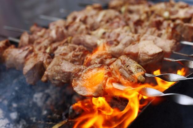 Barbecue in de natuur in de zomer. varkensvleesvlees in de rook op de steenkolen, gezond voedsel, close-up. Premium Foto