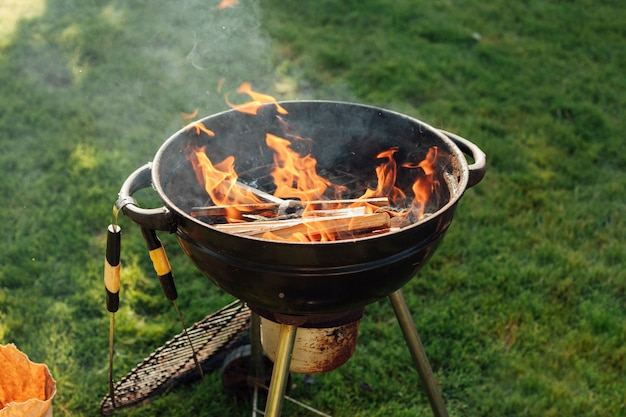 Barbecuegrill met vuur op gras bij park Gratis Foto