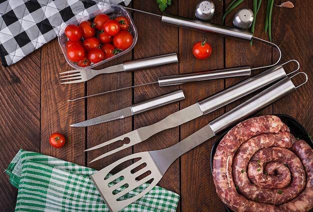 Barbecuehulpmiddelen en worst op houten lijst Premium Foto