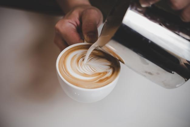 Barista die cappuccino maakt. Gratis Foto