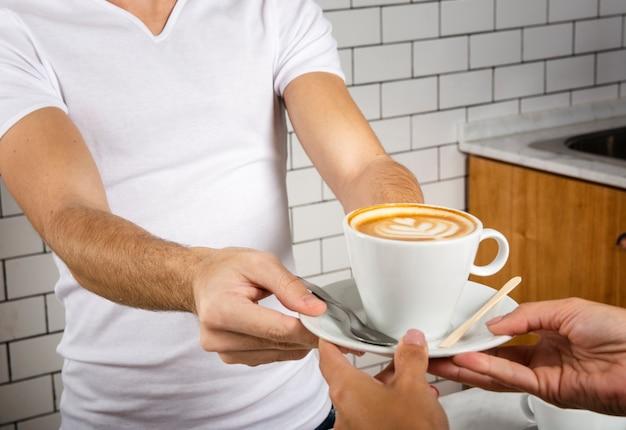 Barista die een kopje koffie aanbiedt aan een persoon Gratis Foto