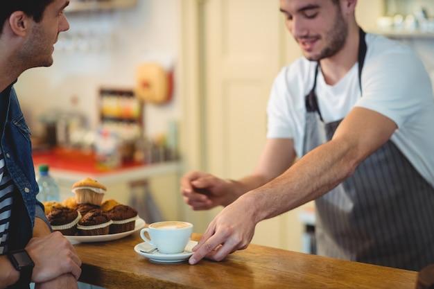 Barista die koffie geven aan klant bij koffie Premium Foto