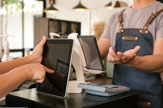 Barista gebruikt het scherm om bestellingen van klanten te ontvangen. Premium Foto