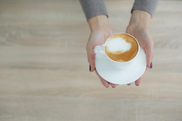Barista in schort in koffiehuis geeft net gebrouwen verse koffie aan klant Premium Foto