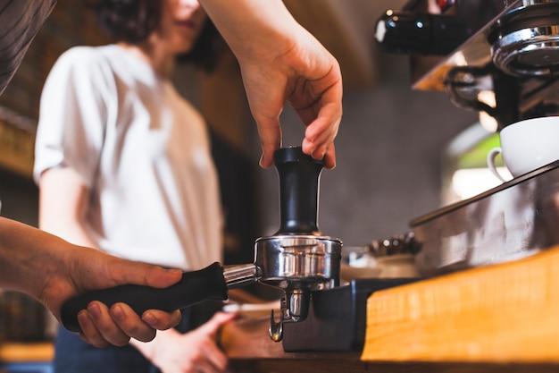 Baristahand die cappuccino in koffiewinkel voorbereiden Gratis Foto