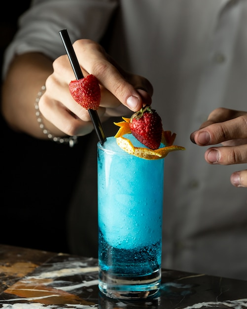 Barman bereidt blauwe cocktail gegarneerd met sinaasappelschil en aardbeien Gratis Foto