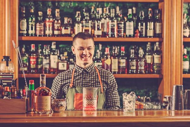 Barman biedt een alcoholische cocktail aan de bar aan de bar Gratis Foto
