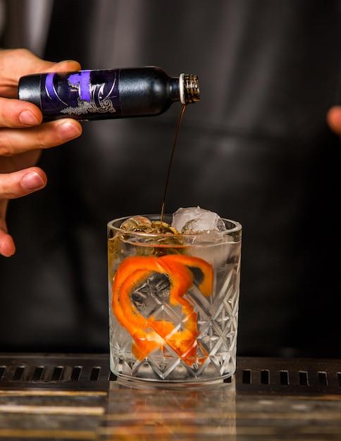 Barman die alcoholische drank in een glas met kokosnoot, gepelde sinaasappel en ijsblokjes toevoegt Gratis Foto