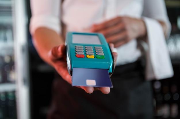 Barman die een creditcard accepteren bij de bar in de bar Premium Foto