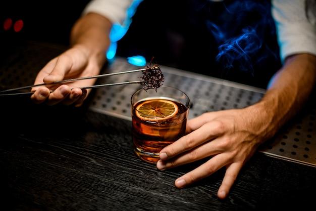 Barman die gekoelde smeltende karamel met twezzers aan de cocktail toevoegen met gedroogde sinaasappel onder blauw licht en rook Premium Foto