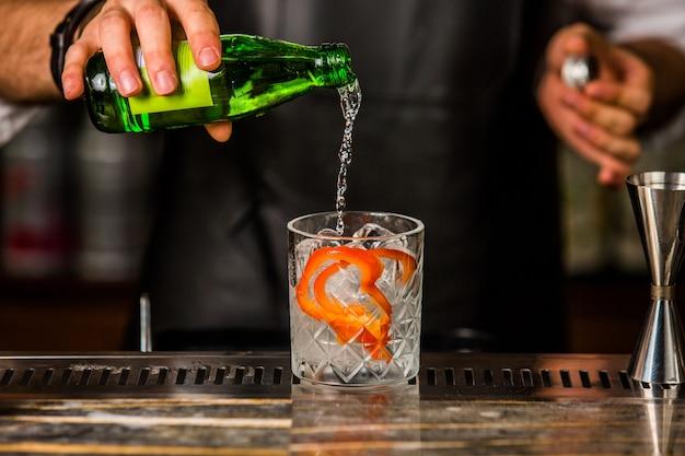 Barman die gin tonic aan het glas toevoegen met ijsblokjes en gepelde oranje schil Gratis Foto