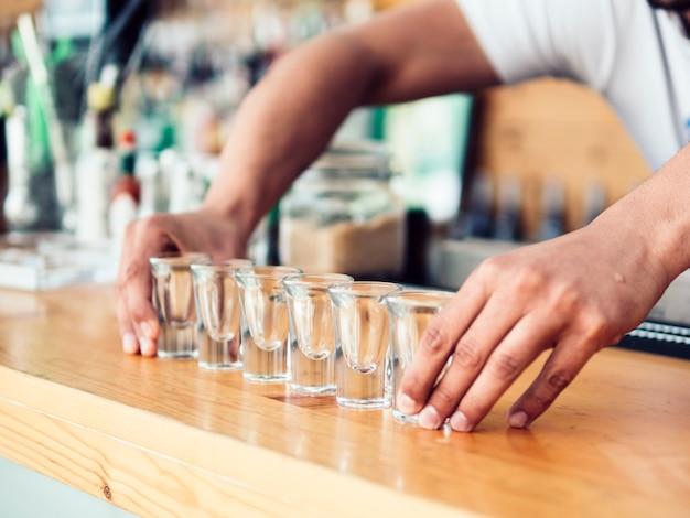 Barman die rij van goglazen op teller zet Gratis Foto