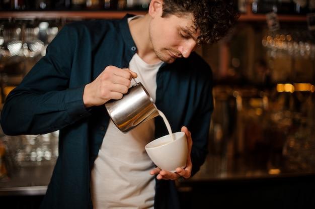 Barman die wat melk van waterkruik in een kop giet Premium Foto