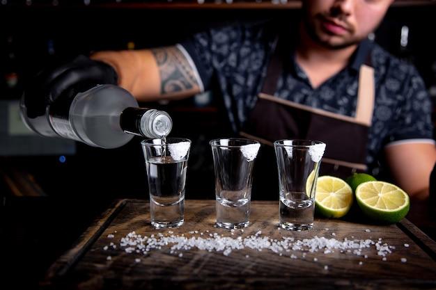 Barman giet harde alcohol in kleine glazen Premium Foto