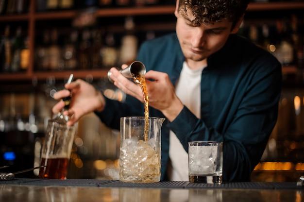 Barman gieten zoete siroop in een pot met ijs en maken een alcoholische drank Premium Foto