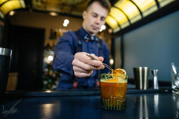 Barman maakt cocktail aan de bar. Premium Foto