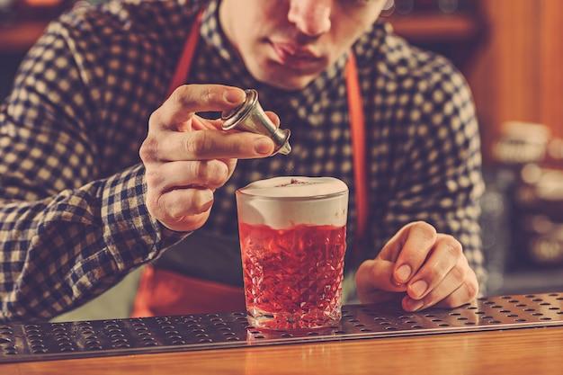 Barman maakt een alcoholische cocktail aan de bar op de bar Gratis Foto