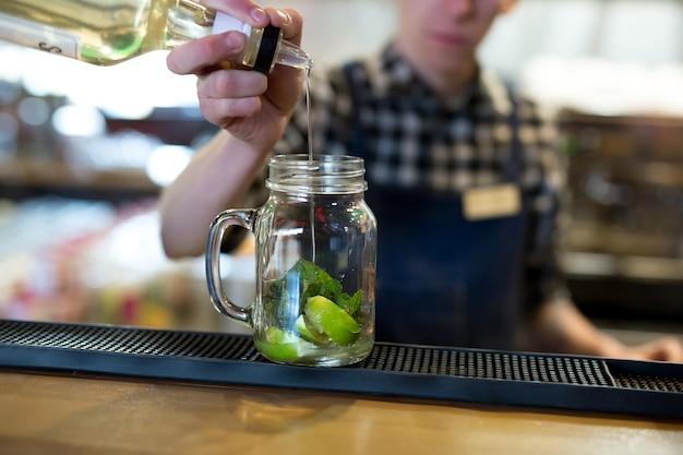 Barman maakt een cocktail aan de bar in het restaurant. Premium Foto