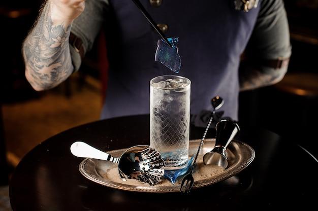 Barman met tattoo versieren verse en zoete zomercocktail met blauw stuk karamel op het dienblad Premium Foto