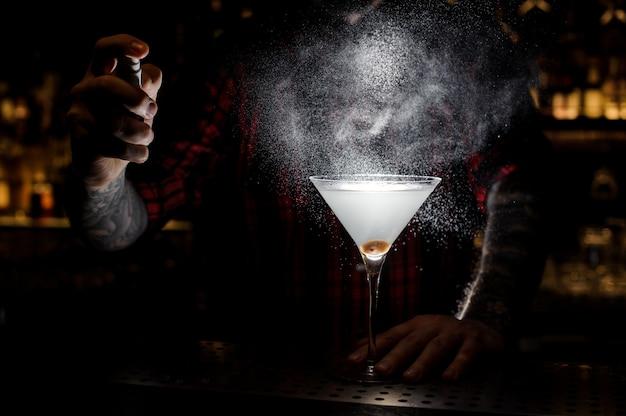 Barman sproeien bitter op het glas met verse cocktail Premium Foto