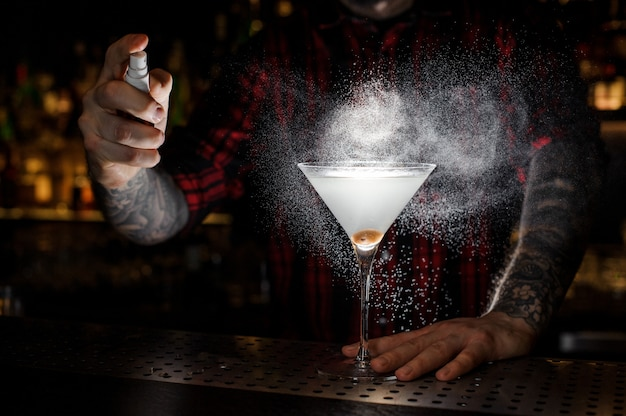 Barman sproeien bitter op het glas Premium Foto