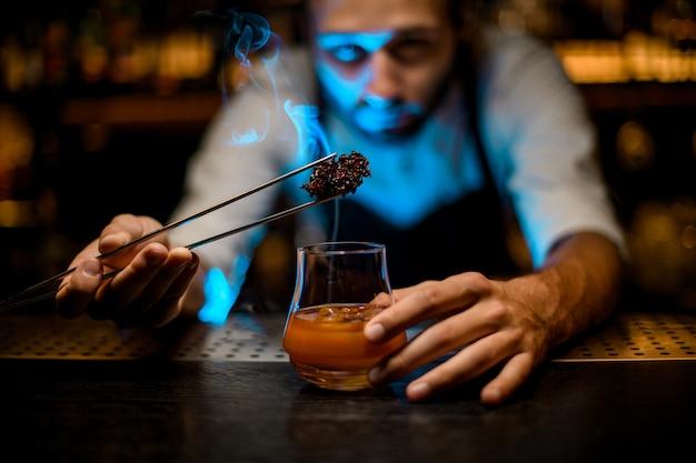 Barman voegt gekoelde smeltende karamel met twezzers toe aan het cocktailglas met ijsblokjes onder blauwe lichten Premium Foto